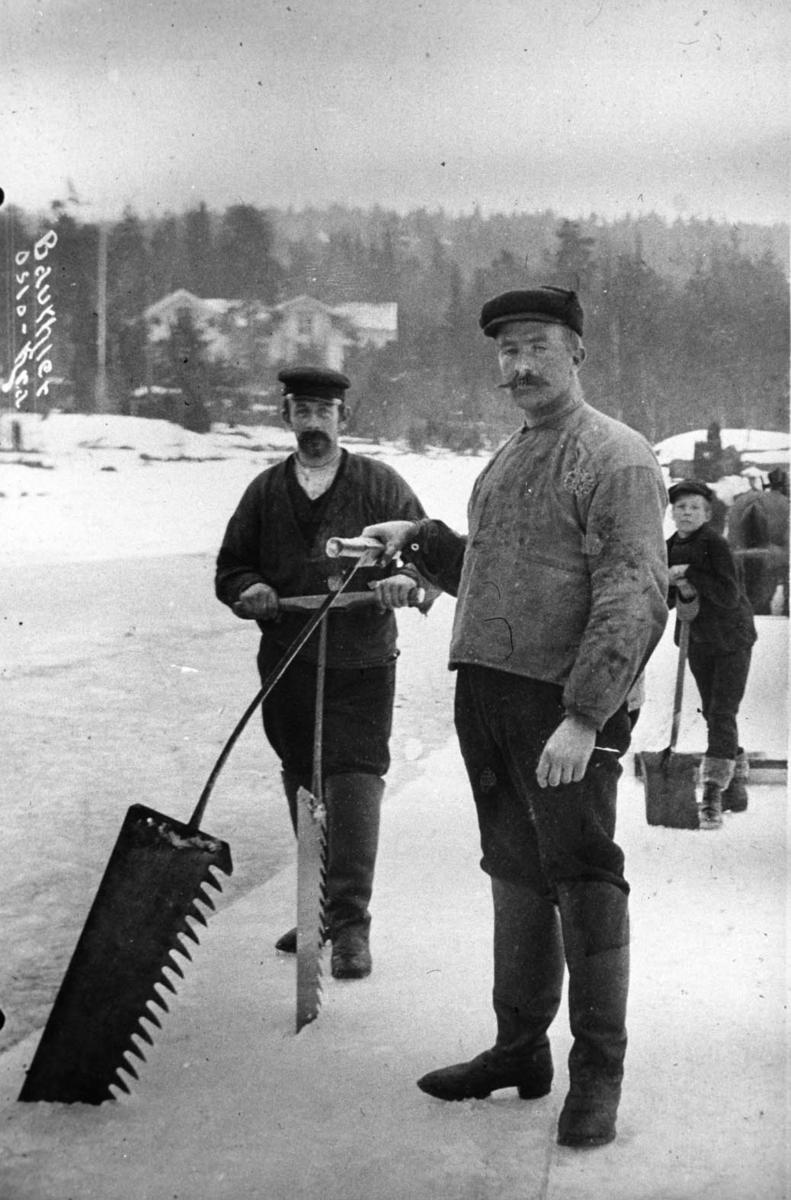 To menn som skjærer is. Mann med sneskuffe i bakgrunn