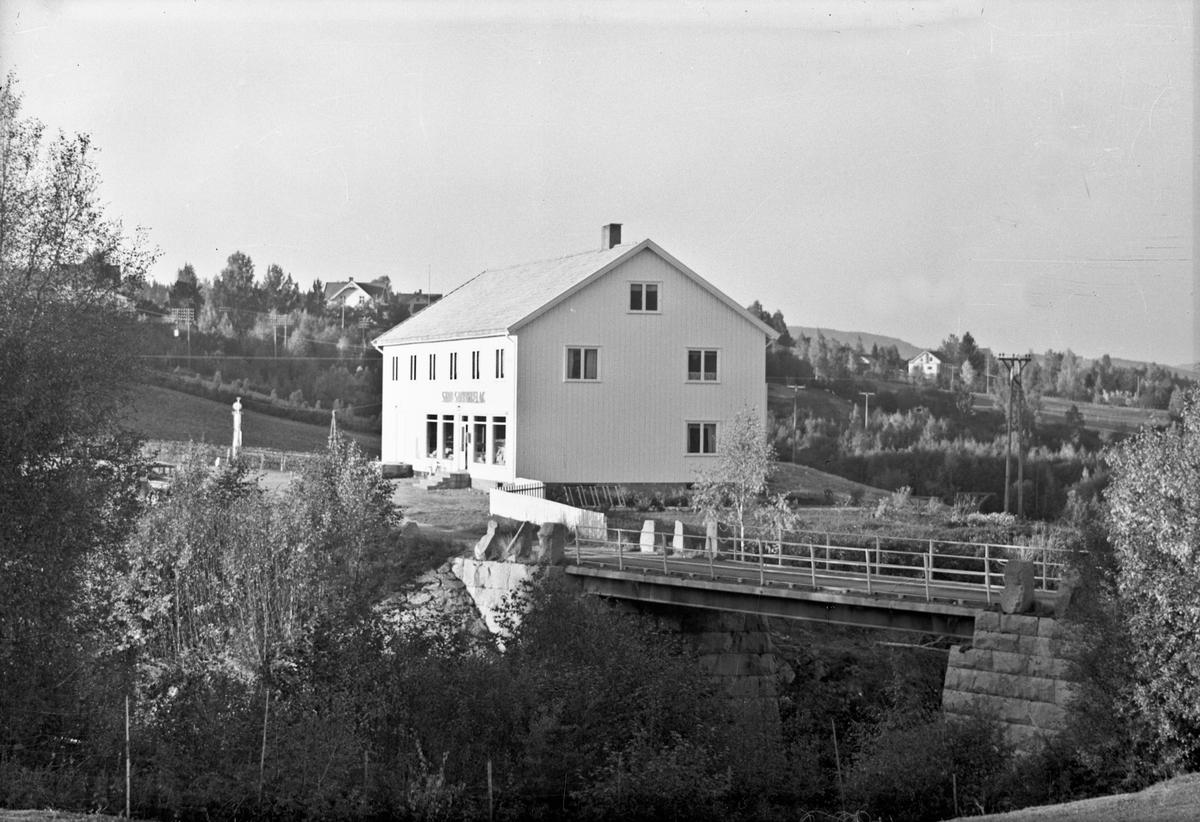 Sand? Samvirkelag ved elv. 1920-30 talls bilmodell og bensinpumpe utenfor.