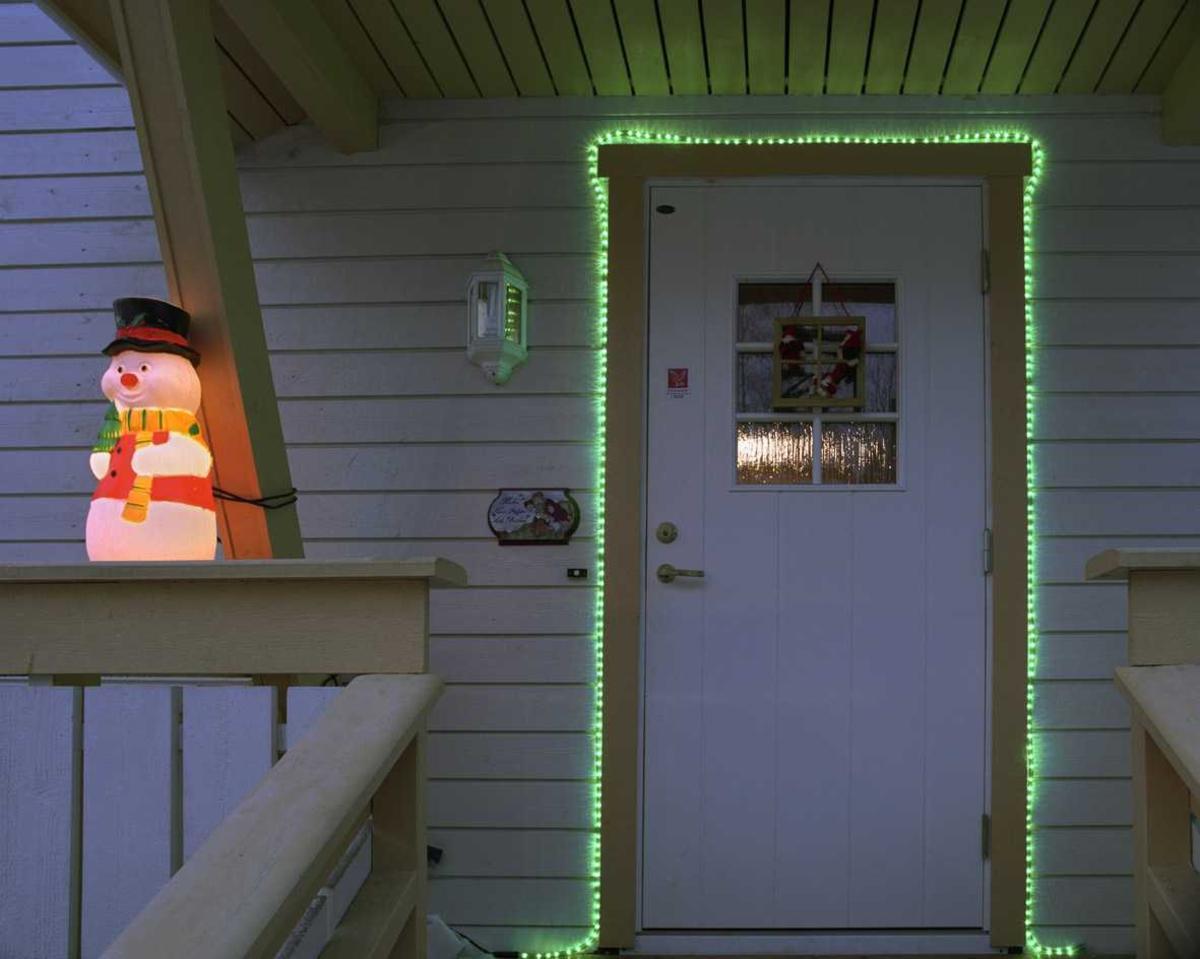 Julebelysning  Lysende grønn lysslange og lysende nisse ved inngangsparti ved enebolig i kjede