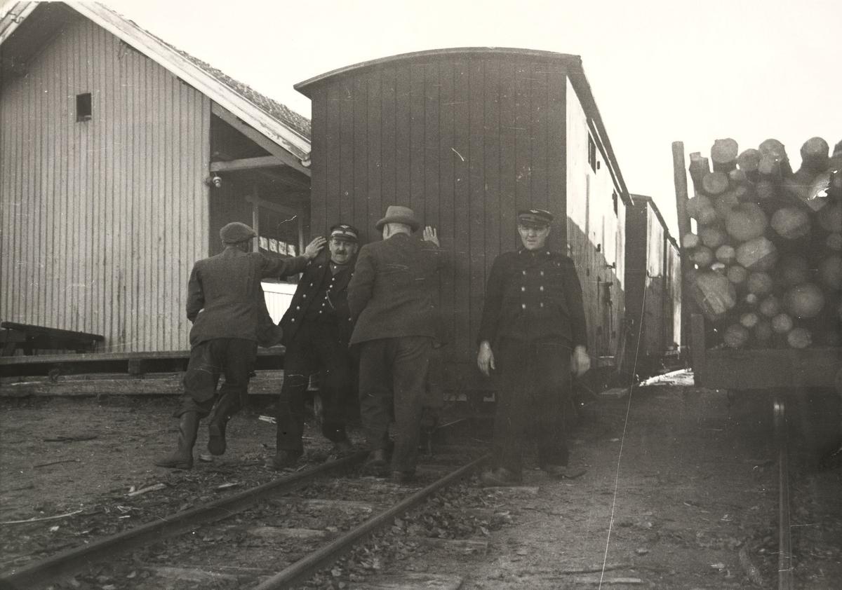 Godsvogn skiftes med håndmakt in på pakkhussporet på Hemnes, To lokale beboere hjelper til.Tog til Skulerud.