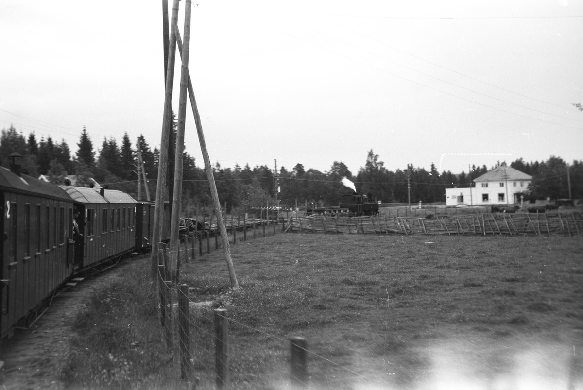 Tog 2051 retning Skulerud,  Ved innkjøringen til Mork stasjon. Mork landhandleri i bakgrunnen.