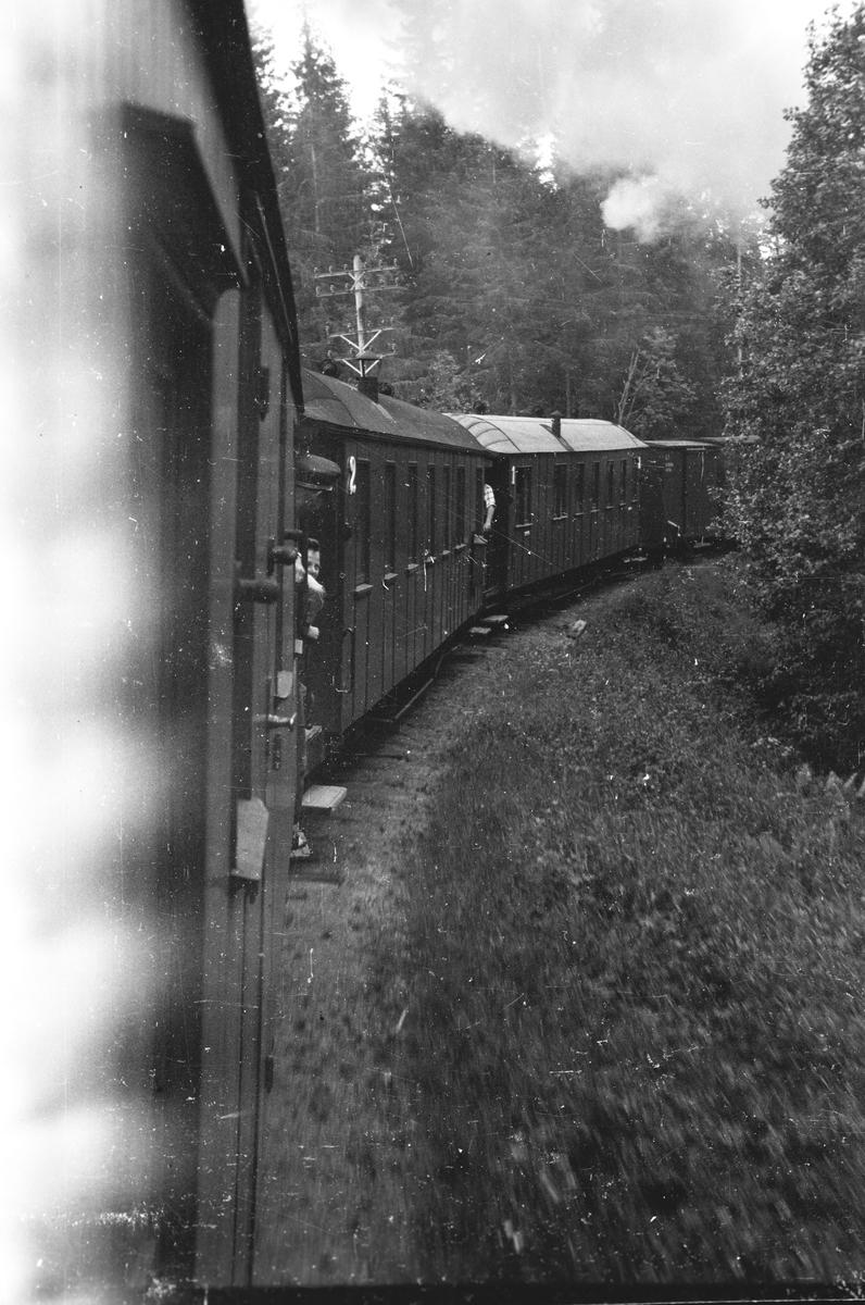 Tog 2051 retning Skulerud. På vei opp Harkerudbakken. Lok 7 Prydz, Vogn To53 (?),  ..., ..., ..., G57, G7, BCo4, BCo3 og CFo5. Løftekasse 231.