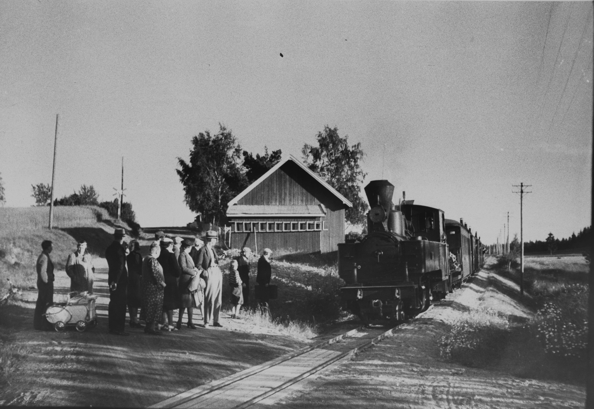 Tog retning Sørumsand stopper for påstigning på Furulund planovergang og holdeplass. Lokomotivet fyres med ved, og frontlykten på lokomotivet er blendet.