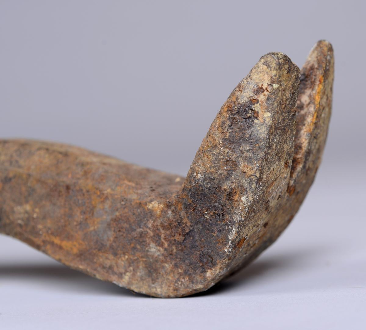 Avlangt spett for arbeid ved jernbanen. Formen er stort sett rund, i den ene enden er metallet formeti en rett vinkel og splittet i to. Redskapet er laget for å ta opp dogg.