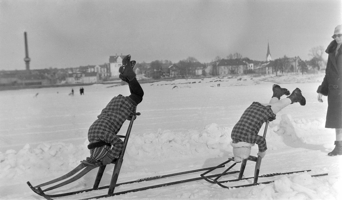 To barn driver med akrobatikk, står på hodet, på spark på Mjøsisen.