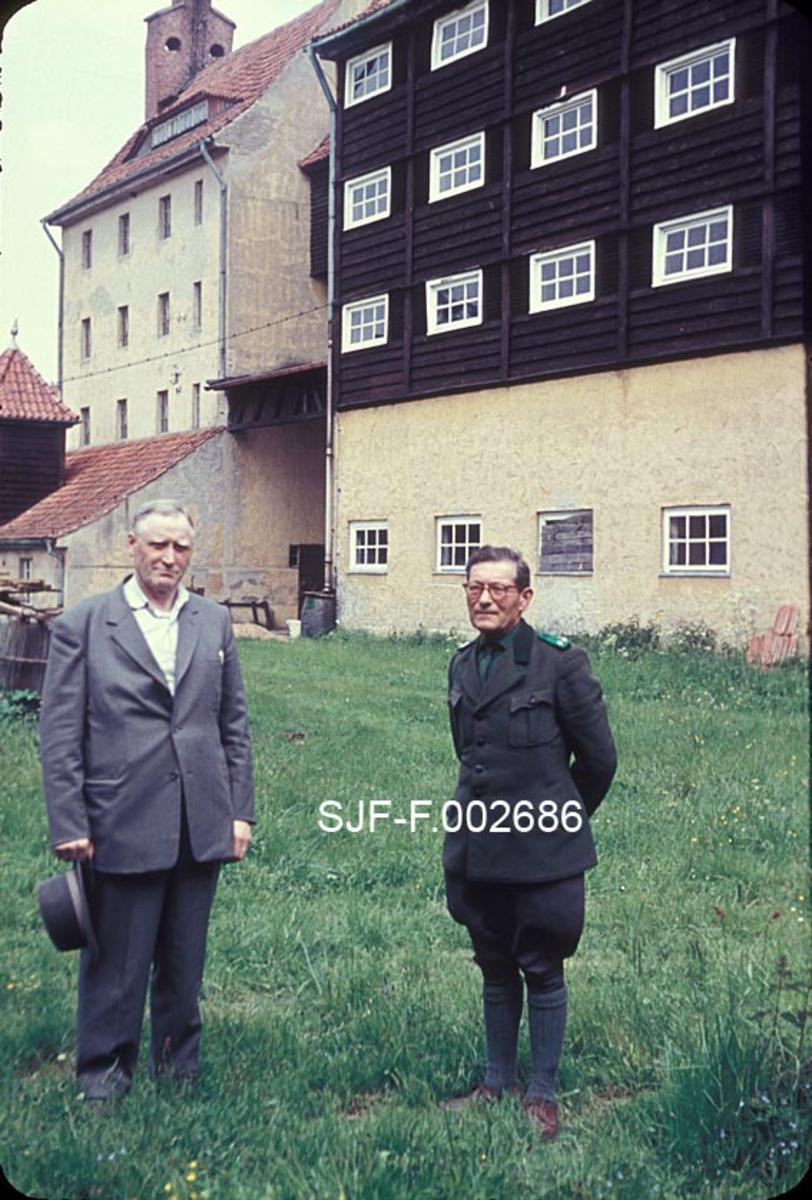 Bestyreren for Statens Skogfrøverk på Hamar, Charles D. Kohmann (til venstre), fotografert sammen med sin tsjekkiske kollega Steinke foran klenganlegget i Jatznick. Kohmann er kledd i grå dress, mens den tsjekkiske forstmannen er iført uniform.  Bak karene ser vi klenganlegget.  Nærmest en høy, murt sokkel med tre etasjer i tre over, bakenfor en fireetasjes, pusset murbygning med bratt teglsteinstak.  Jatznik-klenga var et mønsteranlegg, og fagmiljøet her var kjent for sin organisatoriske dyktighet.  Fotografiet er antakelig tatt omkring 1960.