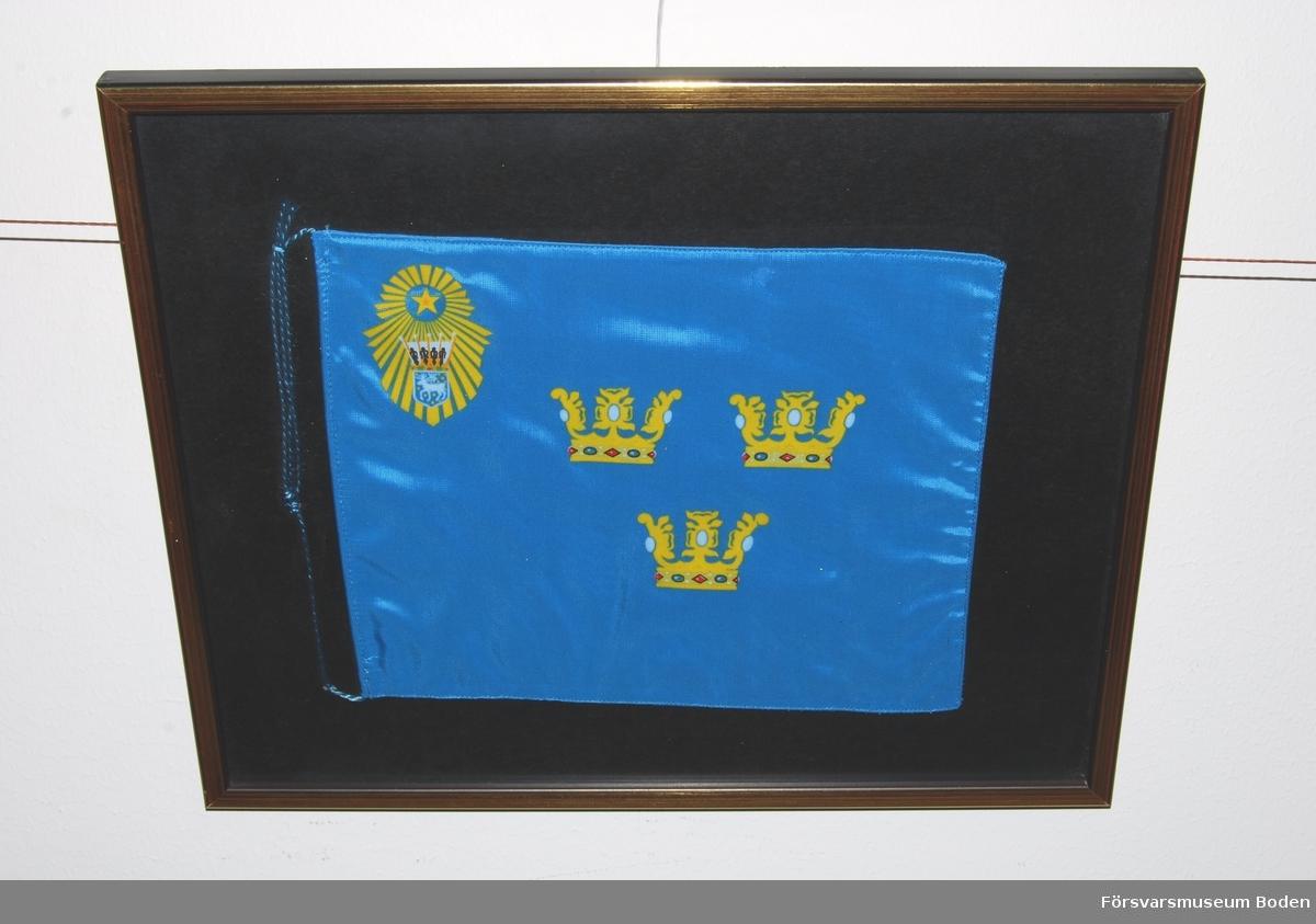 Inramad bordsfana, ljusblå med tre gula öppna kronor i mitten. Övre vänstra hörnet försett med gul stjärna omgiven av strålknippe, vars nedre del innehåller landskapet Västerbottens vapen krönt med hertigkrona. Den ursprungliga fanan överlämnades 1935 av konung Gustaf V.