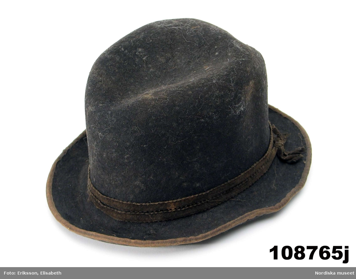 """Hel mansdräkt bestående av 12 delar. a. skjorta b. rock av svart kläde c. väst av svart kläde d. knäbyxor av sämskskinn e. förskinn f. 1 par strumpor vita g. handskar av sämsskinn h. 1 par skor i. hatt j. hatt k. långhalsduk l. löskrage. /BEEL  a. Mått: längd: 96 cm. Längd: 52 cm - ärmlängd. Vidd: 52 cm - ärmvidd Material: Textil, linne. Lingarn - broderier, band. Teknik: Handvävning. Gåsögon. Trådbundet broderi. Broderi - plattsöm. Handsömnad Rak mansskjorta i handvävt hellinnetyg, vävt i gåsögon.  Båltyget i ett stycke, sidosömmar med 13 cm långa sidosprund. Öppning fram, 31 cm långt sprund. Rektangulärt halsspjäll,  rynkningar mot 8,5 cm hög krage med broderier på både in- och utsida i kanten, plattsöm och trädsöm, nuggor i katnen. Två fastsydda mönstervävda knytband, blå/vit och vit. Vidsydd ärm med ärmspjäll. Rynkningar mot 1,3 cm bred ärmlinning broderad med plattsöm och trädsöm, nuggor i kanten,  mönstervävda knytband.. Skjortan är handsydd. /Inga-Lill Eliasson 2007-04-17   f. 1 par strumpor  skaftlängd 40 cm, fot 26 cm; tvåändsstickade av vitt ullgarn i slätstickning. g. h. i. j.Hatt, svart rundkullig filthatt, kullens höjd 14 cm, brätte bredd 5 cm; lätt uppböjt brätte kantat med bomullsband, delvis fodrad med ljust bomullstyg. /BEEL k.Längd: 139 cm. Bredd: 18,5 cm. Material: Halvlinne. Telnik: Handvävning, dräll. Handsömnad. Långhalsduk vävd i dräll, avlång,  randigt mönster av ca 1,3 cm breda ränder i dräll med tuskaft emellan. Handsydd smal fållad kant. Anm: Något gulnad. /INEL l. Löskrage """"hassdutj"""" längd 34 cm, bredd 8,7 cm, rak remsa av vit fin linnelärft, broderi i plattsöm längs långsidorna med små """"nuggor"""" i kanten. Baksida av en bit linneväv med ränder i kypertvariation, knytband i ändarna av mönstervävt linneband i ljusgrått och vitt.  Berit Eldvik maj 2006"""