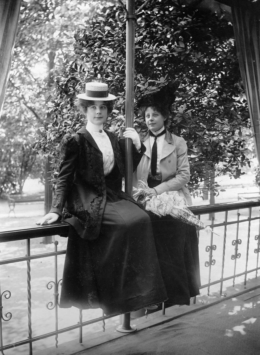 Två unga kvinnor i dräkt och hatt sittande på räcke.