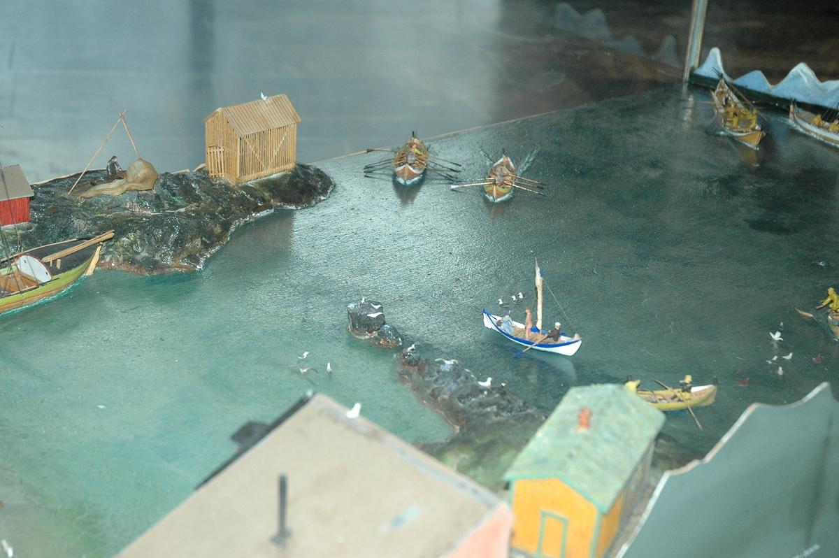 Viser fiskevær i Bø i Lofoten, glasskasse med stålunderstell. Viser landskap med sjø, båter og hus, noe menneskelig aktivitet.