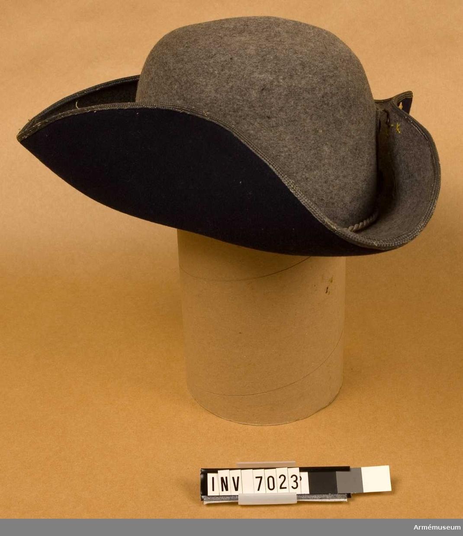 """Officershatt. Grå trekantig hatt med brättet fodrat med mörkblått kläde. På vänster sida en gul kokard 40 mm diameter samt """"tre kronor"""" av gul metall. Som kantband på brättet en mattförgylld galon. (Numera ser den silverfärgad ut på hatten. Men ser man på insidan, så..). Brättena kan fällas ned och döljer då det """"svenska märket"""". Till parad isättes en ståndare i fickan på kullens vänstra sida. För att befordra luftväxlingen finns i hattkullen två ventiler som vid behov kan täppas till. Inuti hatten finns två hakremmar, som kan använda vid behov. Svettremmen är ljus och dess fastsättniing döljs av en grå silkesnodd runt brättet. Storlek 57, färg Q M."""