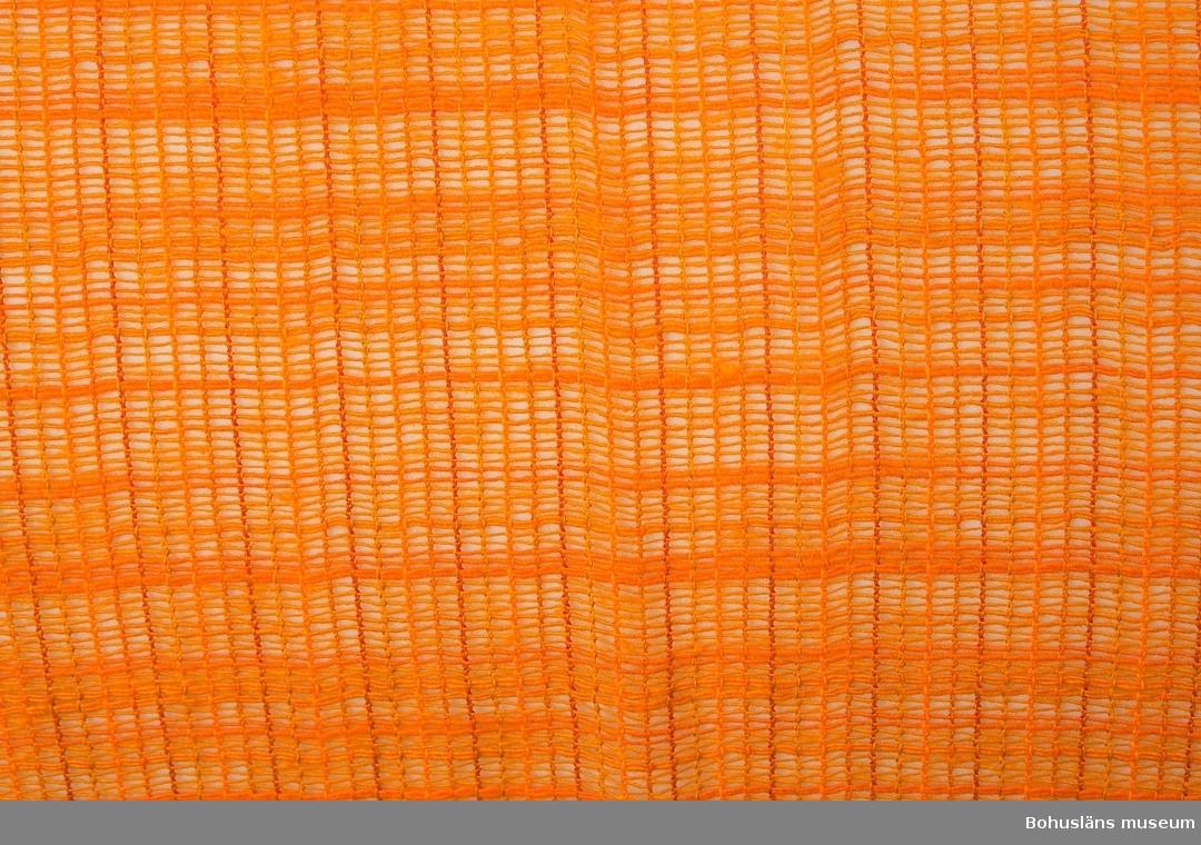 Glest vävd gardin (par) av syntetfiber i intensivt orange färg i något svagt varierande nyanser. En typisk färg för inredningsdetaljer från omkring mitten av 1960-talet till början av 1970-talet. Upptill tunnel för gardinstång. Nedtill 42 cm bred fåll, troligen tillkommen för att korta gardinerna.                                                Personuppgifter och fakta kring samlingen se UM025572.