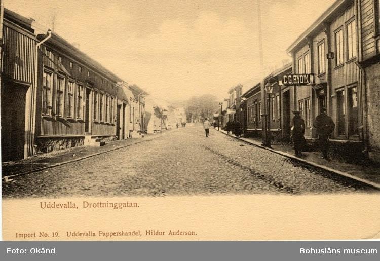 """Tryckt text på vykortets framsida: """"Uddevalla, Drottninggatan."""" """"Uddevalla Pappershandel, Hildur Anderson."""" Till höger i bild hänger en skylt med texten C. G. Rydin"""