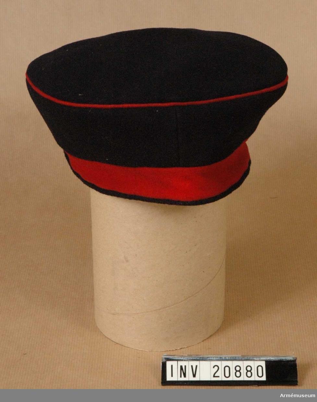 """Grupp C I. Lägermössa, menig, Gardesreg t fot, Tyskland. 1877.Tallriksmodell. Av tyg, försedd med ett 2,5 cm långt bräm, rött till färgen, samt svart passpoal längs nedre kanten. Kullen är svart och övre kanten har röd passpoal. Foder av grov linnelärft. I botten finns påskriften """"II.GR."""" =II:a Gardesregement, """"1877"""", """"Berlin"""", (svårläst). LITT  Geschihte der Bekleidung und Ausrüstung der Königlichen Preussischen Armaée in den Jahren 1808 bis 1878. Berlin 1878. Paragraf 588. Sida 12. Efter dagorder av 25/4 1867 blev möss- bottnens diameter 1,5 cm längre än den övre kantens. Das Ehrenkleid des Soldaten. M Lezoius, Sida 150: Olika mössor. Das Deutsche Reichsheer. G Krickel, Berlin. Sida 19. Kokarden för lägermössa infördes efter dagorder av den 16/6 1842.Enl kapten W Granberg."""