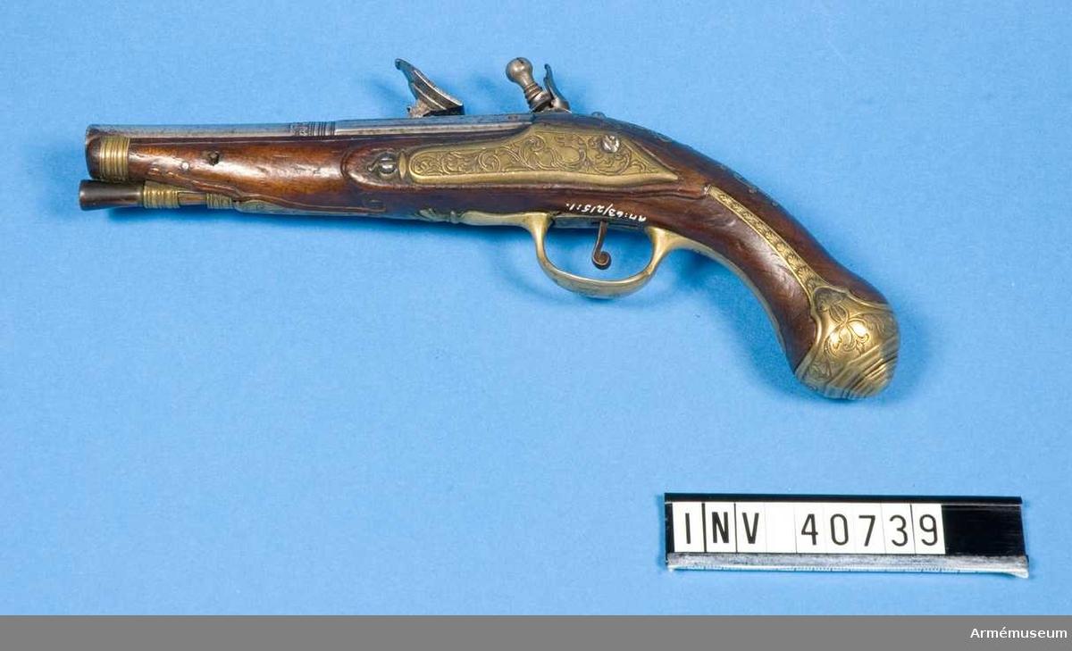 Grupp E III. Flintlåspistol, tillverkad omkring 1770-80 i Italien.  I par med AM.040740. Pipan är rund med ett 6 cm långt åttkantigt kammarstycke. De tre övre fälten avgränsas från varandre genom en upphöjd kant. Baktill på pipan översidan en förgylld stämpel som troligtvis skall föreställa ett krönt lejonhuvud, samt tre djup instansde punkter. Den är desutom signerad ANGELO LEONI.   Låset är av järn. Det har separat fängpannelock liknande det som förekommer på hjullås. Låsbleck, hans och eldstål har etsad dekor.  Stocken är av polerad valnöt. Beslagen är av mässing med graverad dekor. På kolvhalsen en krönt sköld.