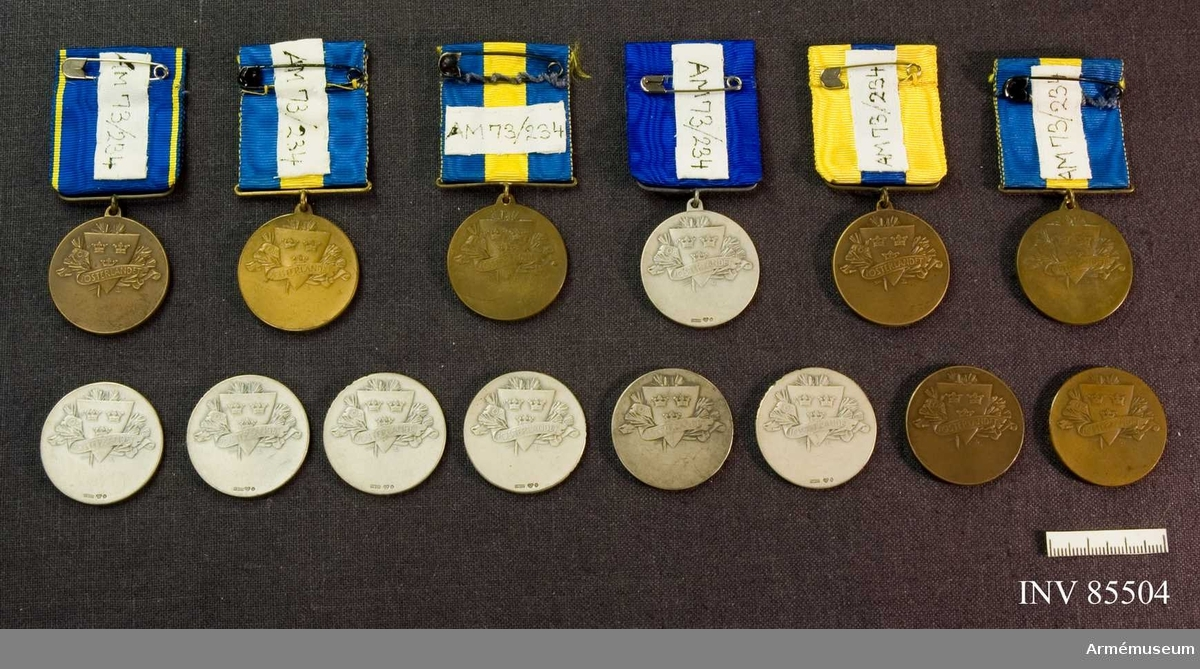 Grupp: M II. Skyttemedaljer: skolungdomens i Sthlm skytteförening silver med mörkblått band, vattrat silver. Brons med blå o blågula band, vattrade brons.