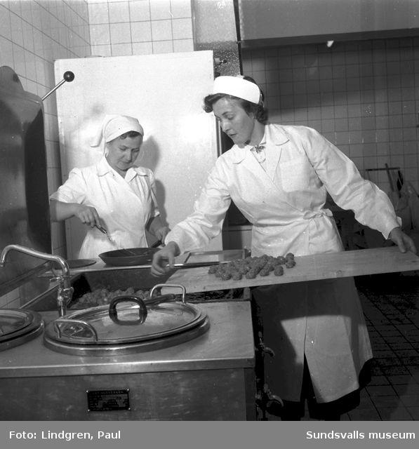 """Korvstoppning"". Kvinnor steker köttbullar i storkök."