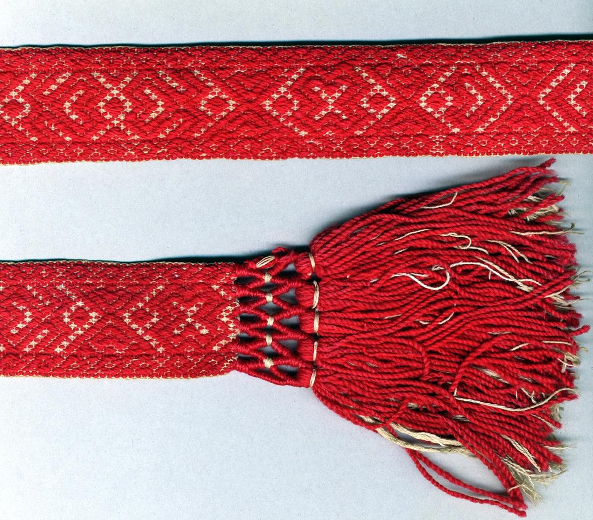 """Livband vävt i opphämta. Rött opphämtamönster på ljus botten. Avslutat i var ände med tofsar (120 mm långa); varptrådarna är omlindade med rött ullgarn och oblekt bomullsgarn vari frans av rött ullgarn samt oblekt bomullsgarn är iknuten. Varp, botten i halvblekt 2-trådigt s-tvinnat bomullsgarn. Varp, mönster i rött 2-trådigt z-tvinnat ullgarn. Två bottenvarptrådar mellan varje mönstervarptråd. Inslag i oblekt 2-trådigt s-tvinnat bomullsgarn. Märkt med påsydd tyglapp med texten: """"Malmöhus Läns Hemslöjdsförening"""". Dessutom märkt med SHR-märke med texten: """"Nr 7 Herrestad"""". Längd inklusive tofsar."""