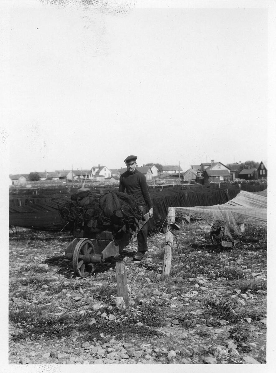 'Akka-expeditionen sommaren 1930: ::  :: Fiskeläget i Träslöv: 1 st man kör skottkärra lastad med drivgarn på väg till torkning. Bakom finns drivgarn uppsatta för torkning och i fonden hus. ::  :: Ingår i serie med fotonr. 2033-2087.'