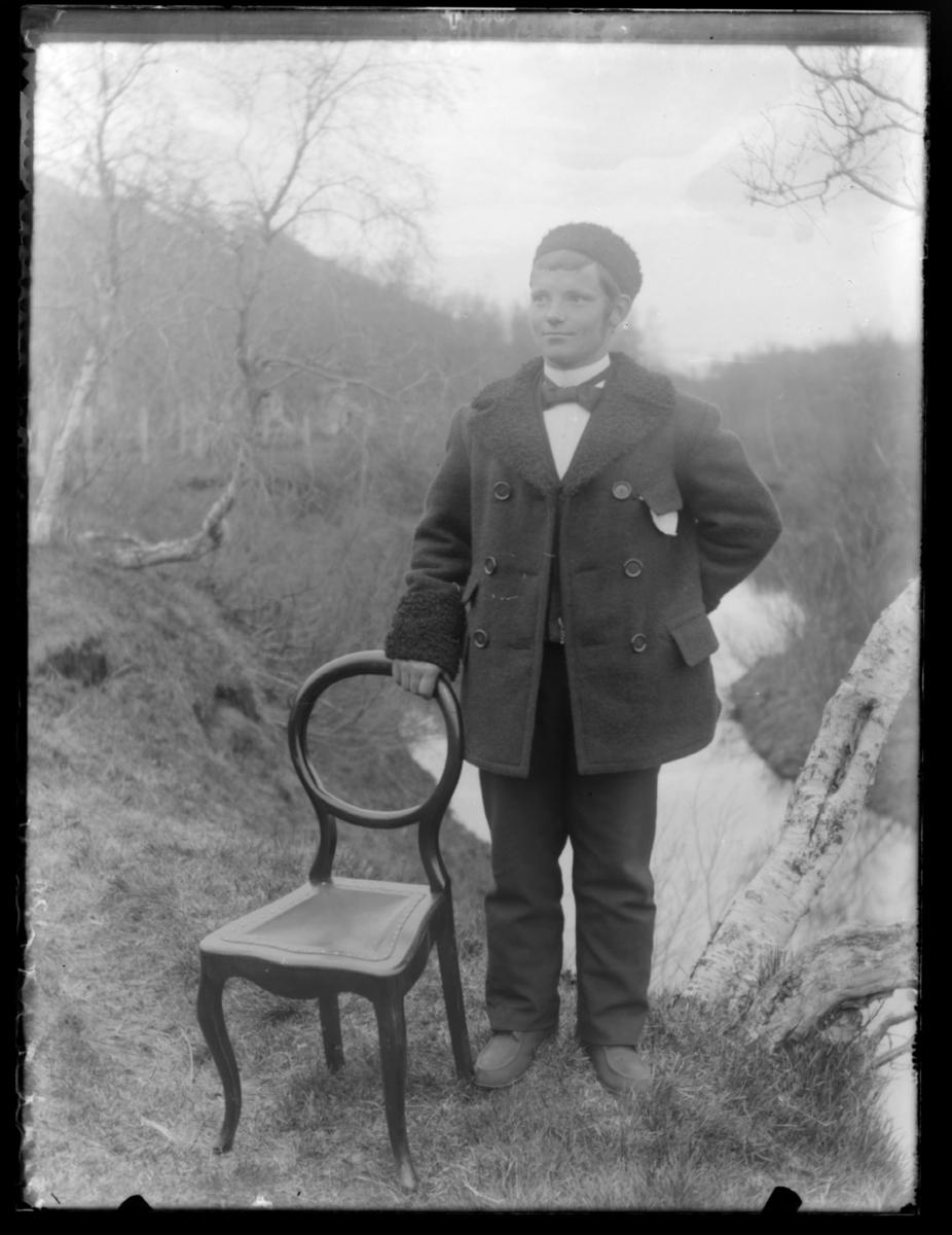 Ung mann stående ute ved en stol