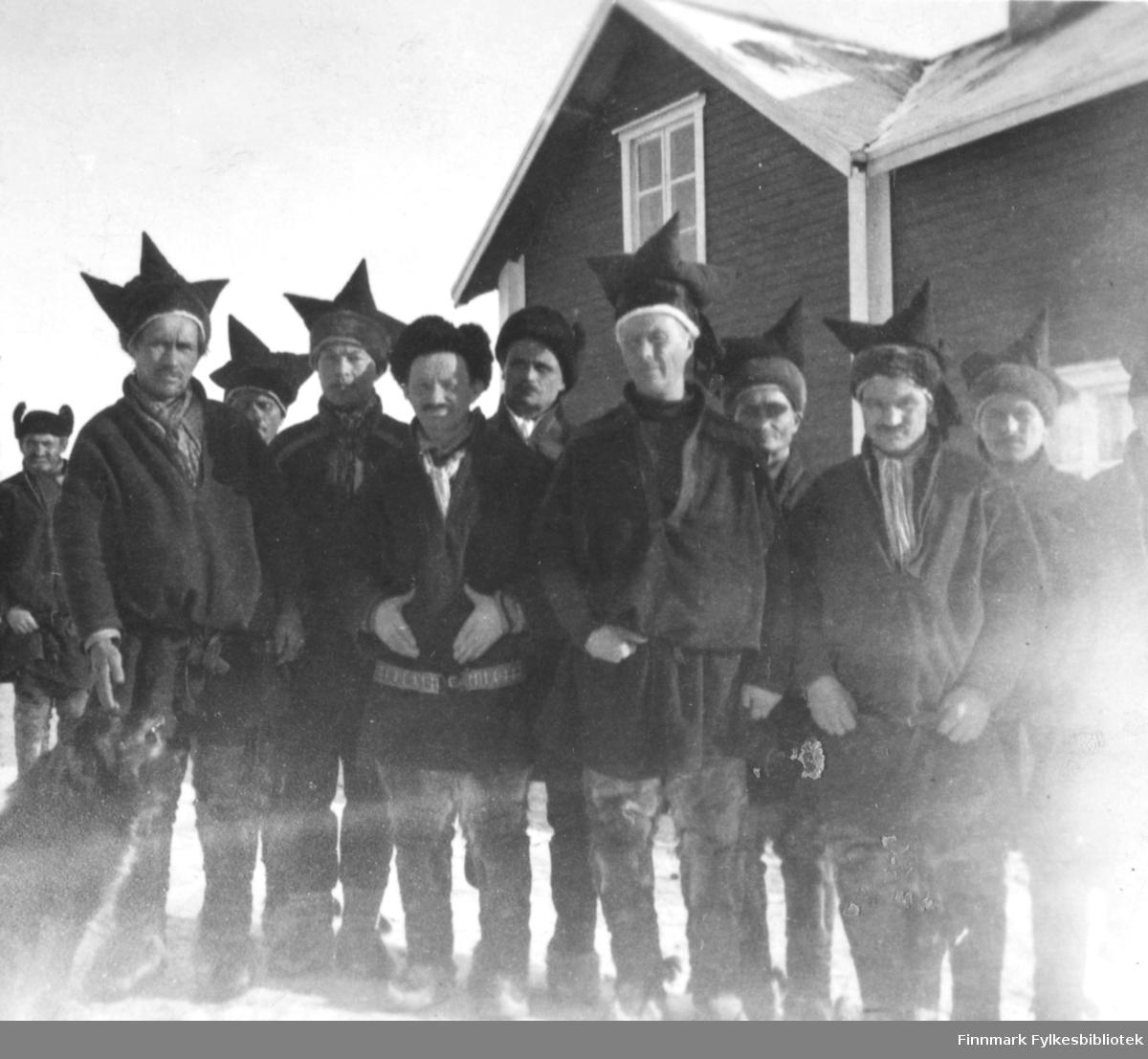 Et gruppebilde fra Utsjoki, Finland. Et gruppe samiske menn står foran et hus. Bildet er et stereobilde.          .