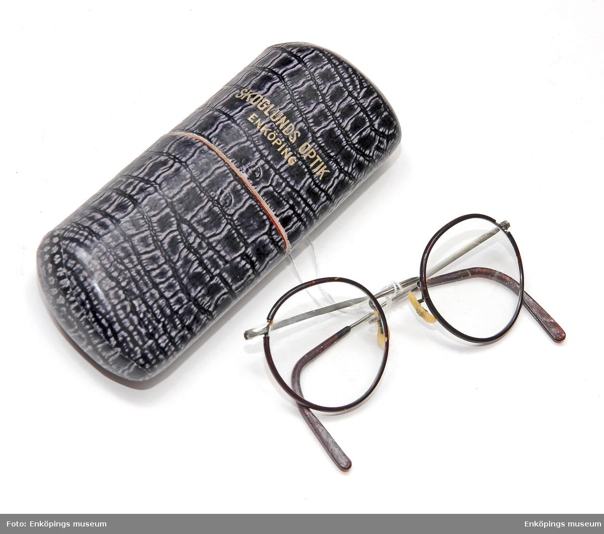 """I ett grå/svart fodral av pressad papp med text i """"guld"""" bokstäver """"Skoglunds Optik, Enköping"""", ligger ett par runda hornbågade glasögon."""