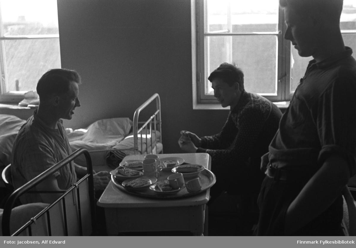 Tre unge menn fotografert på St. Vincents Hospital under krigen. Mannen til venstre sitter i en mørk stol med avrundet rygg. Han har en forholdsvis lys skjorte med oppbrettede ermer på seg. Mannen i midten på bildet sitter litt foroverbøyd med noe i hendene. Han har en mørk, strikket ullgenser på seg. Genseren har lyst mønstre rundt håndleddene, øverst på ryggen og skuldrene. Helt til høyre på bildet står en ung mann lent inn til en sengegavl. Han har en mørk bukse og en litt lysere skjorte med oppbrettede ermer på seg. På gulvet mellom dem står et hvitt/lyst bord med et rundt fat oppå. På fatet står to krus, fem små tallerkener med mat og to kopper. Tre senger vises på bildet. Senga nede til venstre har sortlakkert metallramme. Ved siden av står en seng med hvitlakkert ramme. Oppi ligger hvite sengeklær. Nede til høyre ses den hvite sengegavlen. Rommet er ganske lyst og ensfarget. To vinduer med hvite karmer og stolper ses på veggen. Diffust ses mørke bygninger gjennom vinduet.