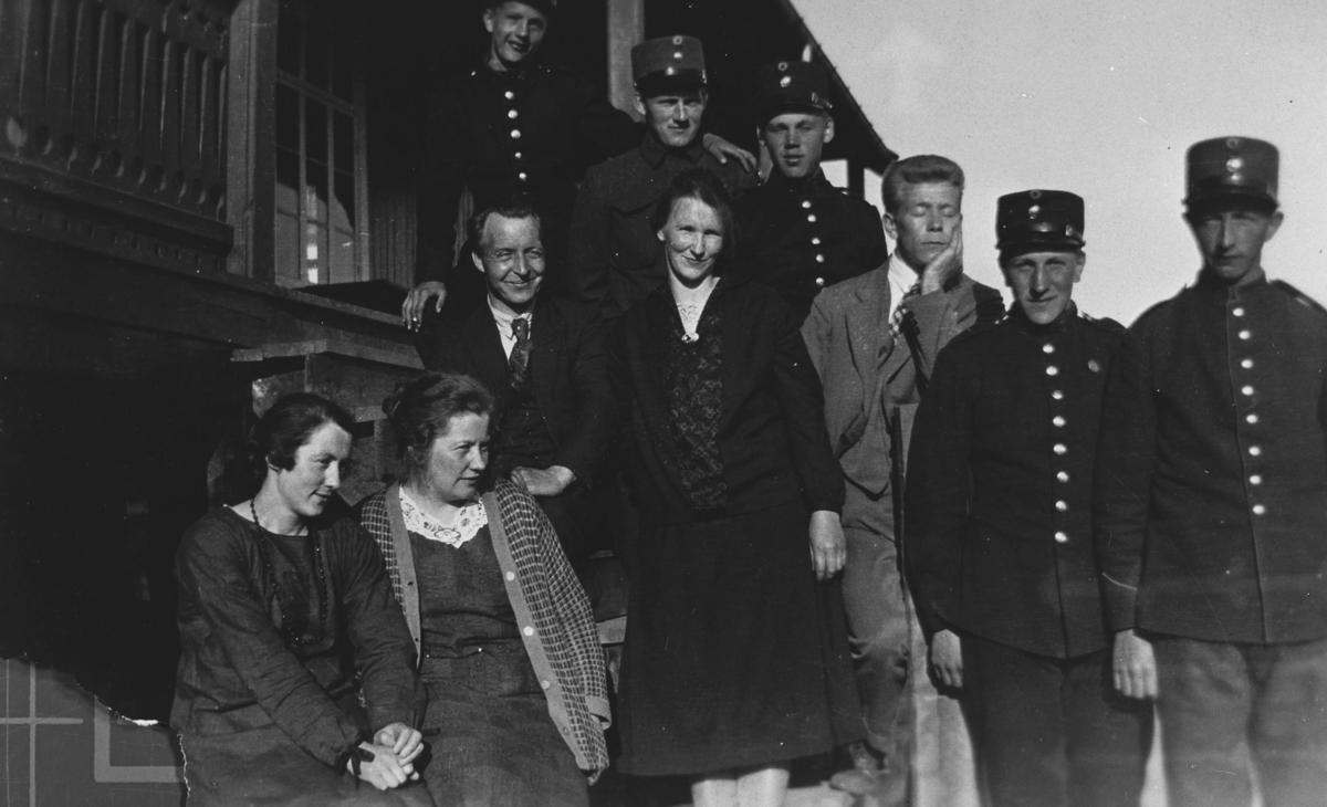 Guppebilde fotografert på trappa i soldathjem i Nyborgmoen. Sivilene fra venstre andre rekke: bestyrer Olav Korsvik, Anna Lande og hennes bror Jak. Lande.  Kvinnene sittende på trappa er kjøkkenpersonale i soldathjemmet, kvinnen til venstre trolig Margit Joki. De fem soldatene i gruppen er ukjente.