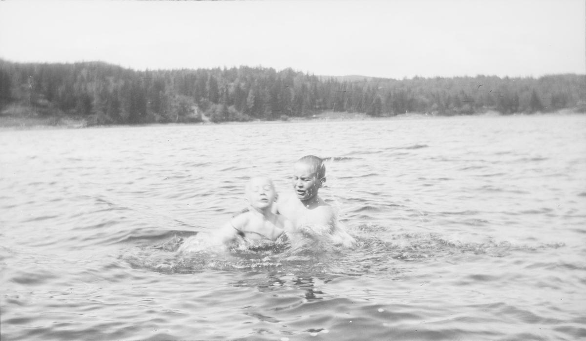 """En eldre gutt hjelper en yngre gutt med svømmetrening i en innsjø på østlandet. Den yngste gutten har på svømmebelte. En """"kruset"""" vannoverflate forteller om litt vind. I bakgrunnen sees skog med noen hogstflater."""