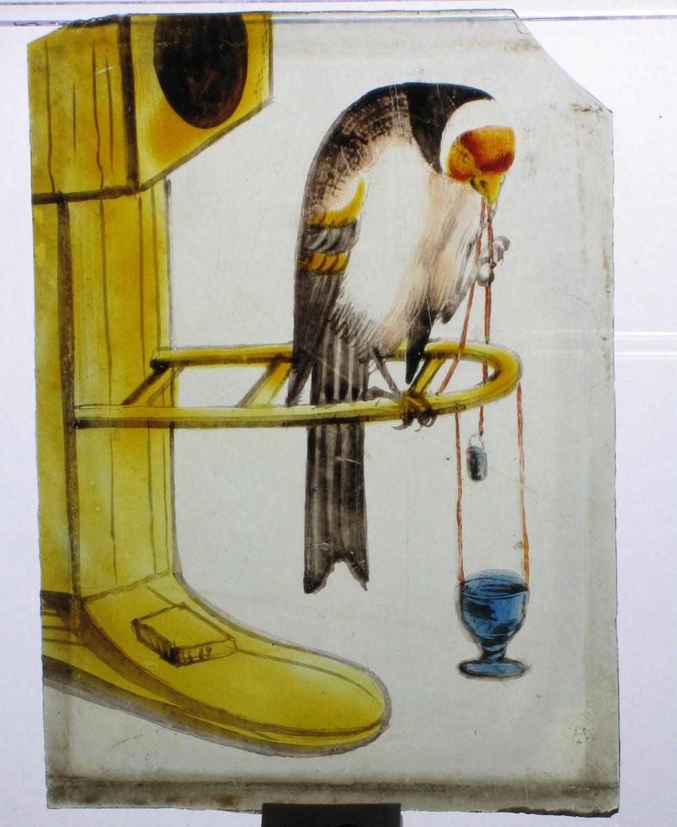 Papegøye på vagle utenfor et oker fuglehus, holder en rød tråd i nebbet, i enden av denne henger et  beger, som den prøver å få ned i et blått kalkformet større beger som også henger i rød tråd. Fuglen er brun  med rødt hodeparti.