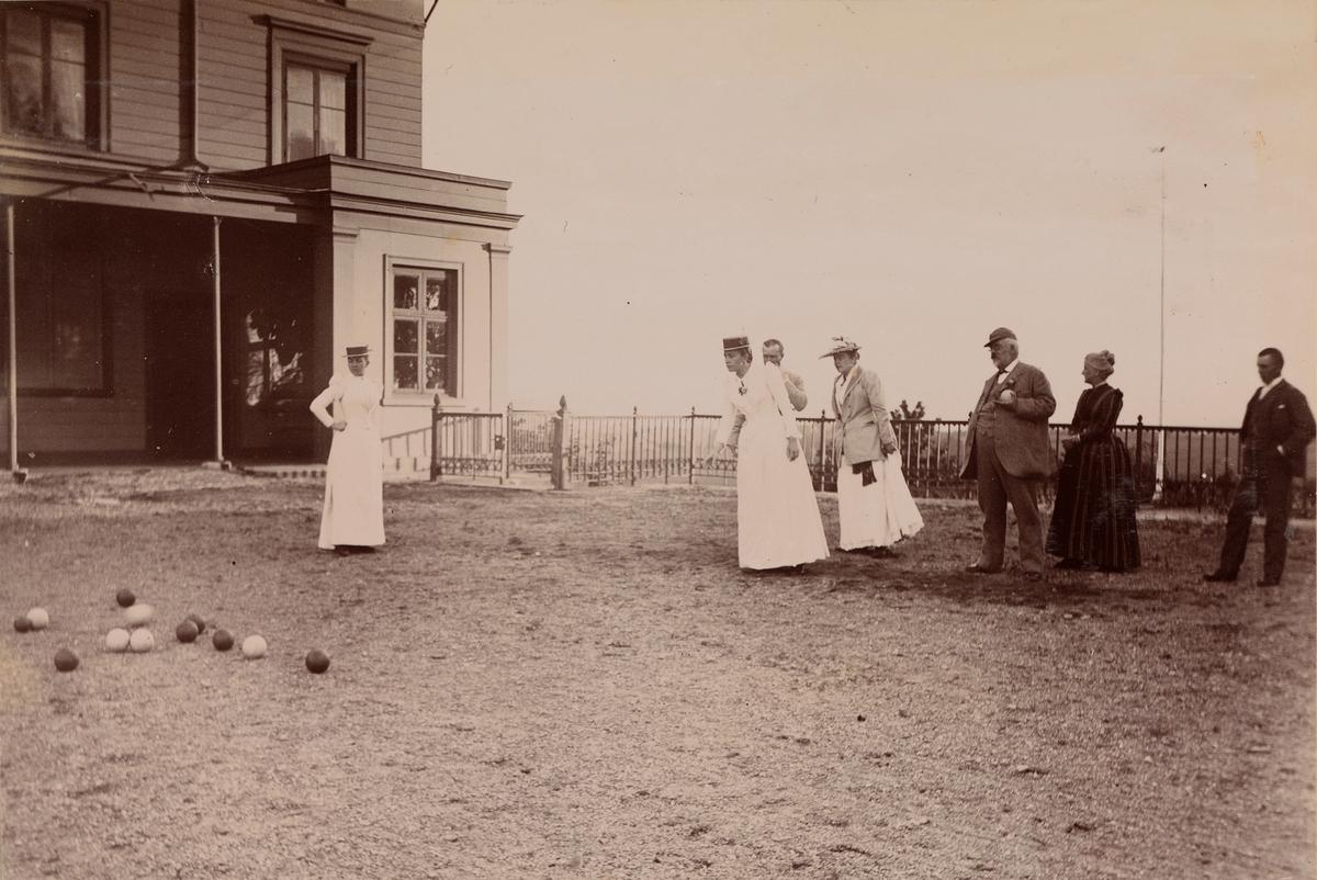 Boccia-spill foran hovedhuset på Linderud Gård, fra venstre: Agnes Mathiesen, Julie Mathiesen, Haaken Larpent Mathiesen, Louise Mathiesen, en uidentisert mann og kvinne, Christian Pierre Mathiesen.