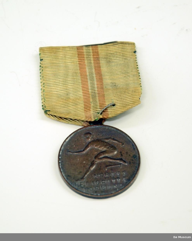 Medalje med innskrift: NORGES FRI-IDRETTS FORBUND Bånd i hvitt, med det norske flaggets farger i en stripe - svært falmet og gulnet.