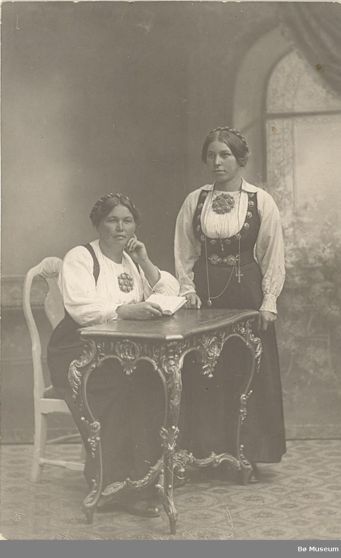 """To yngre kvinner i stakk og liv i fotoatelier. Frå v. """"frk. Sisjord"""" (?)  og Anlaug Glennahaugen."""
