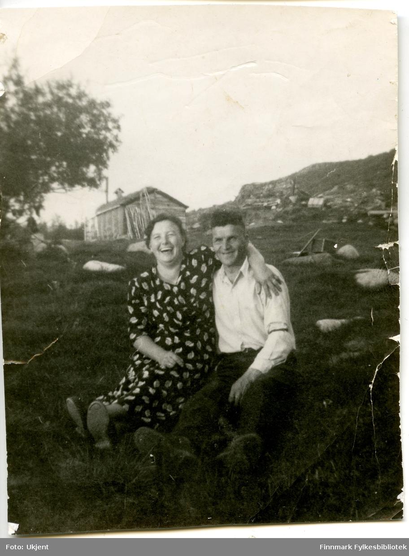 Et portrett av ekteparet Johanna og Petter Aule. Johanna er kledd i kjole, Petter i skjorte og bukse. De sitter i gresset på bakken, og i bakgrunnen kan man se en bygning laget av tre.