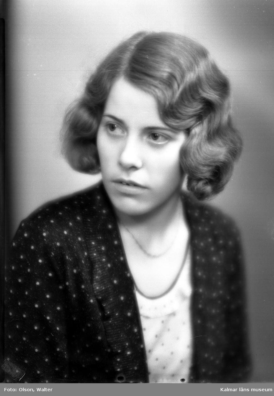 Ateljébild på en kvinna i blus, jacka och ondulering. Enligt Walter Olsons journal är bilden beställd av Greta Westein ifrån Storgatan 15 i Kalmar.