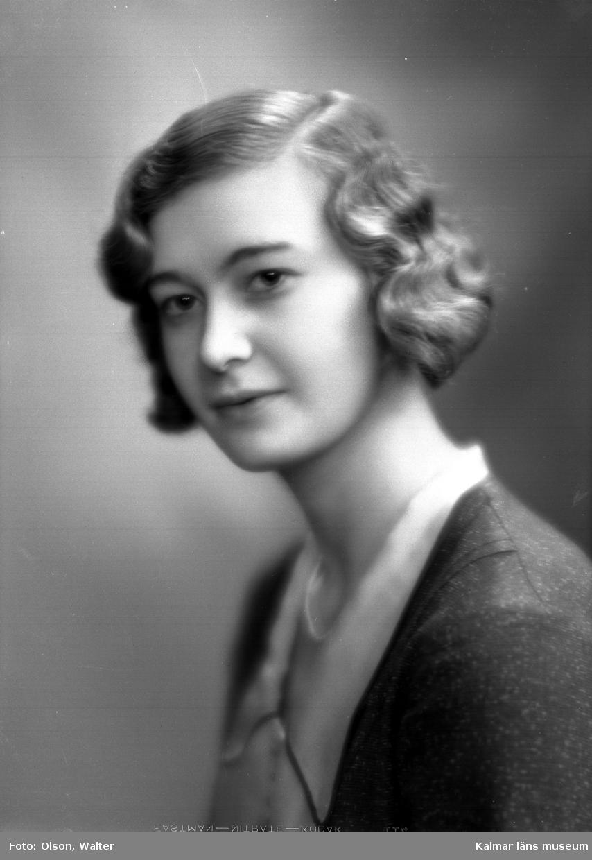 Ateljébild på en kvinna i blus, jacka och halsband. Enligt Walter Olsons journal är bilden beställd av Gunnel Sjöstedt ifårn Smedby.