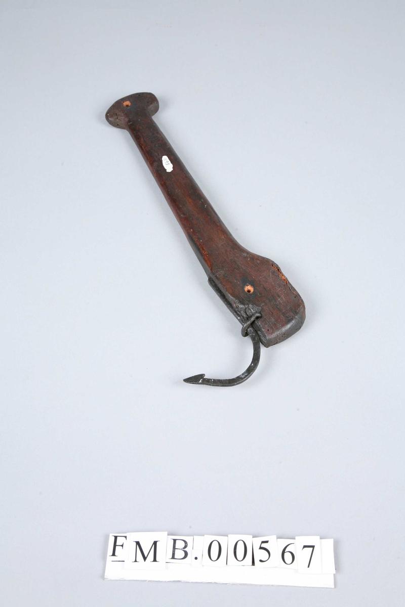 En liten klepp der håndtaket ender i en runding, som det går et hull igjennom. Kroken er vid og har en liten hake på spissen.