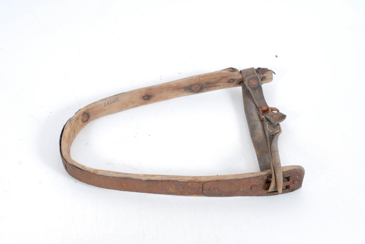 Form: Bøyd trebånd som i nedkant er holdt sammen av en regulerbar skinnrem. Et forsterkende jernbånd er satt på yttersiden av treklaven.
