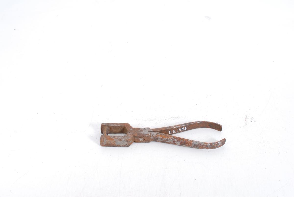 Form: Buede håndtak. Fjærbelastet,men fjærer avbrudt Munningspartiet er rette rektangulære plater, på den ene siden er det en kon spiss. Flatt toppparti. På den andre platen en lav forsenkning.