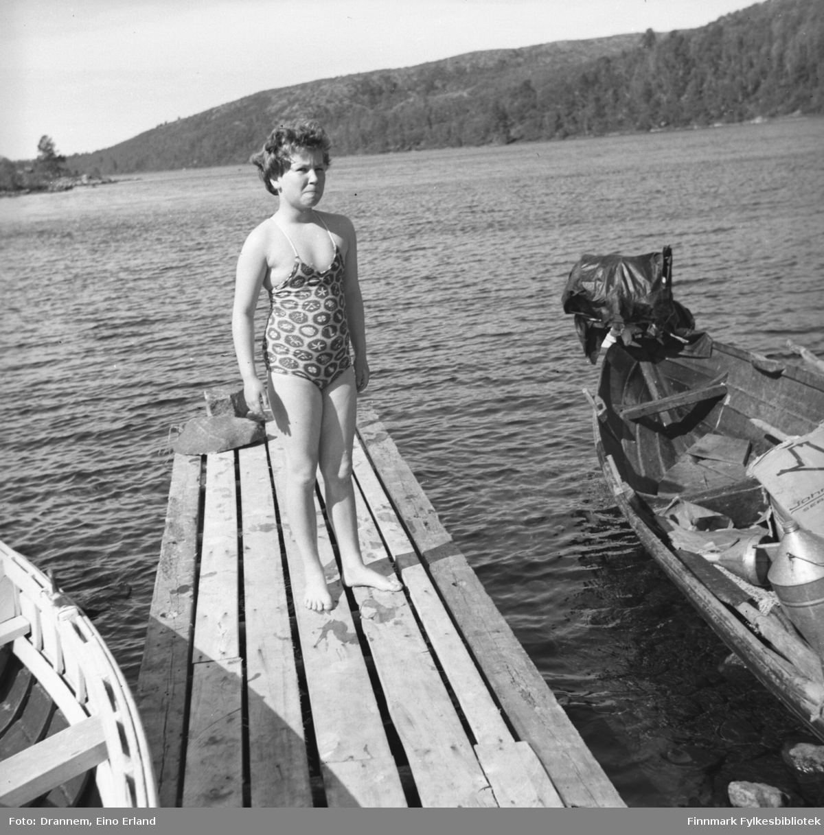 Turid Karikoski står på en liten brygge med to robåter på hver side.
