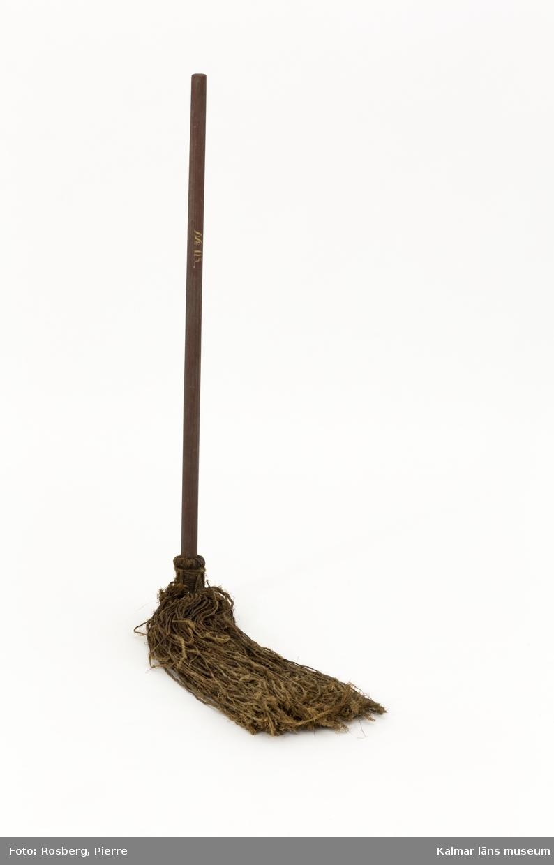 KLM 45847. Av tvinnade snoddar fästa i rödmålat skaft av trä. På skaftet målad text i gult. Text: No 115. Snoddarna är fästa med rep i zick-zack.