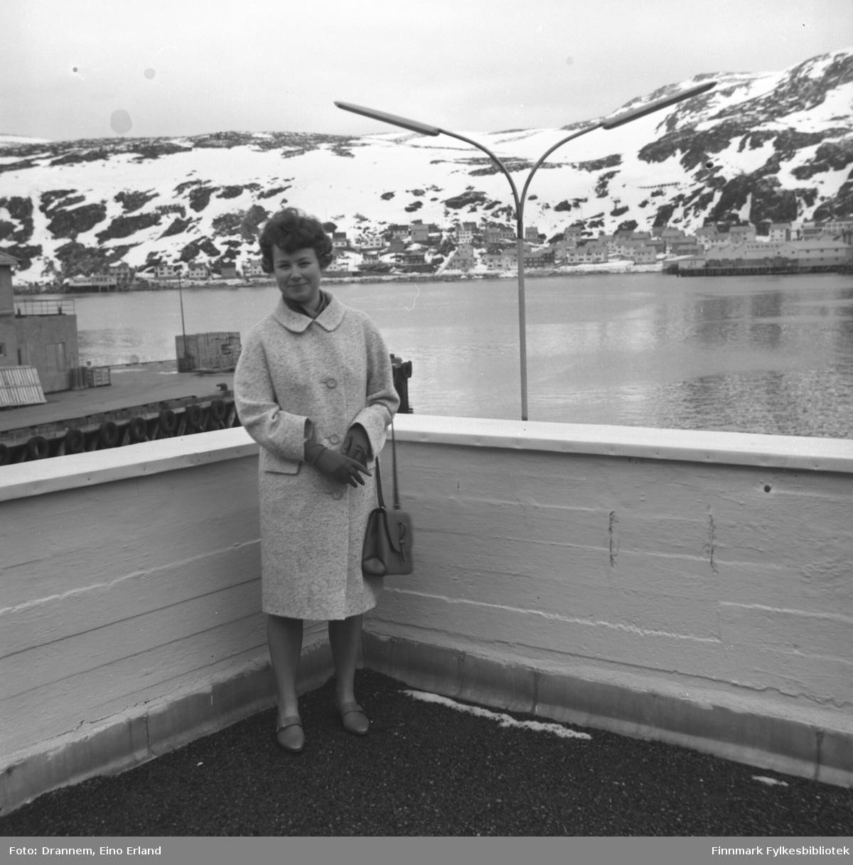 Turid Karikoski står på verandataket til Tollboden i Hammerfest. Bydelen Molla ses i bakgrunnen.