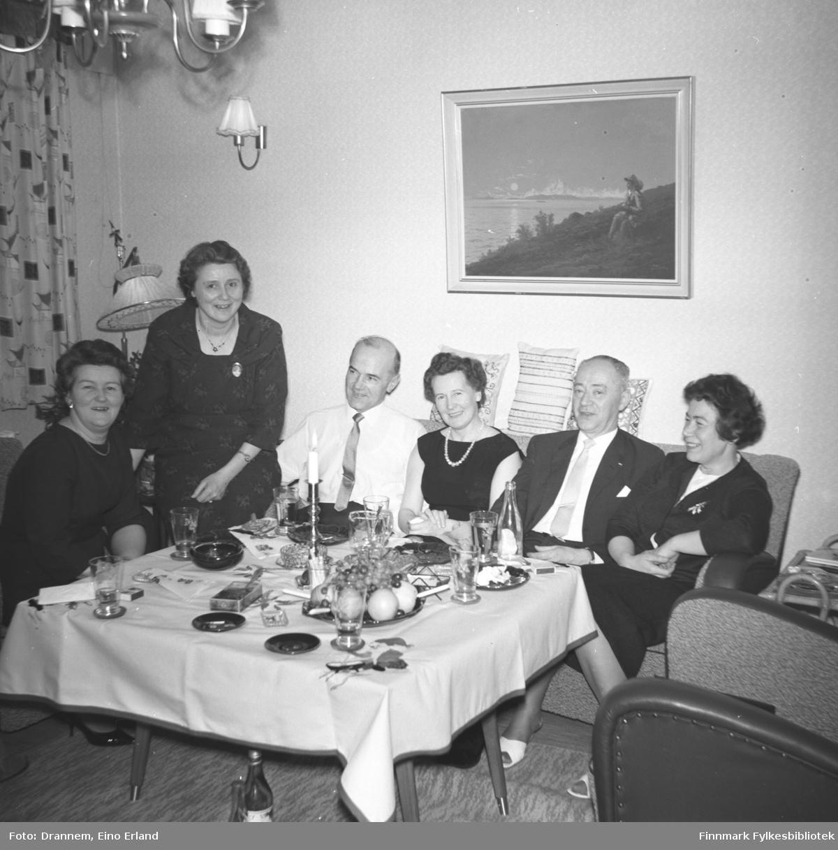 Pentkledte mennesker samlet i stua til familien Drannem i Hammerfest. Jenny Drannem sitter helt til høyre på bildet.