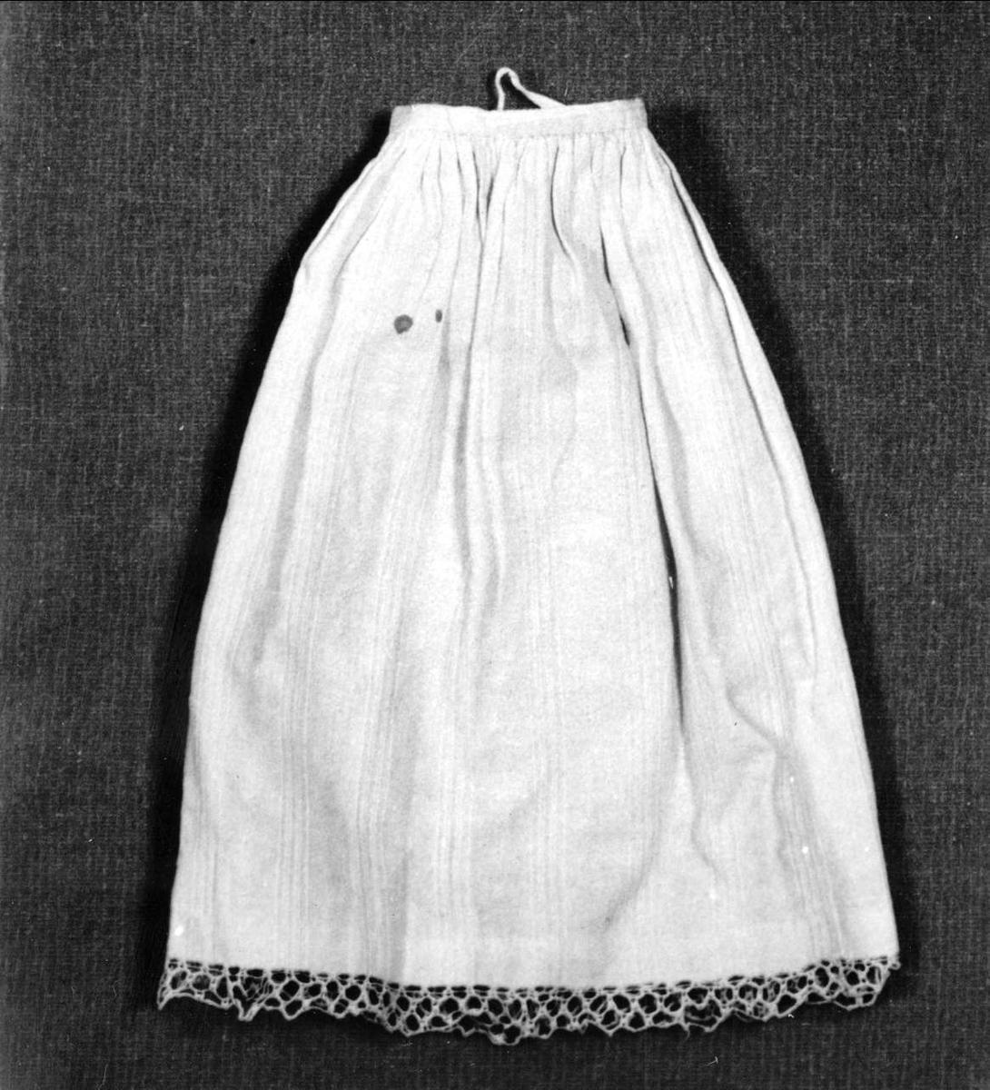 Dockplagg. Underkjol av vitt mönstervävt bomullstyg med spetskant.