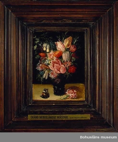 Blomsterarrangemang i glasvas med noppor samt fjäril. Motivet innehåller bland annat olikfärgade tulpaner, en kungsängslilja, en pärlhyacint, en ringblomma, en anemon, fjädernejlikor, viol och rosmarinkvist. På den ljusa bordsytan sitter en nässelfjäril till vänster och till höger om den mörkfärgade glasvasen med noppor som buketten är placerad i ligger en dubbel fjädernejlika.