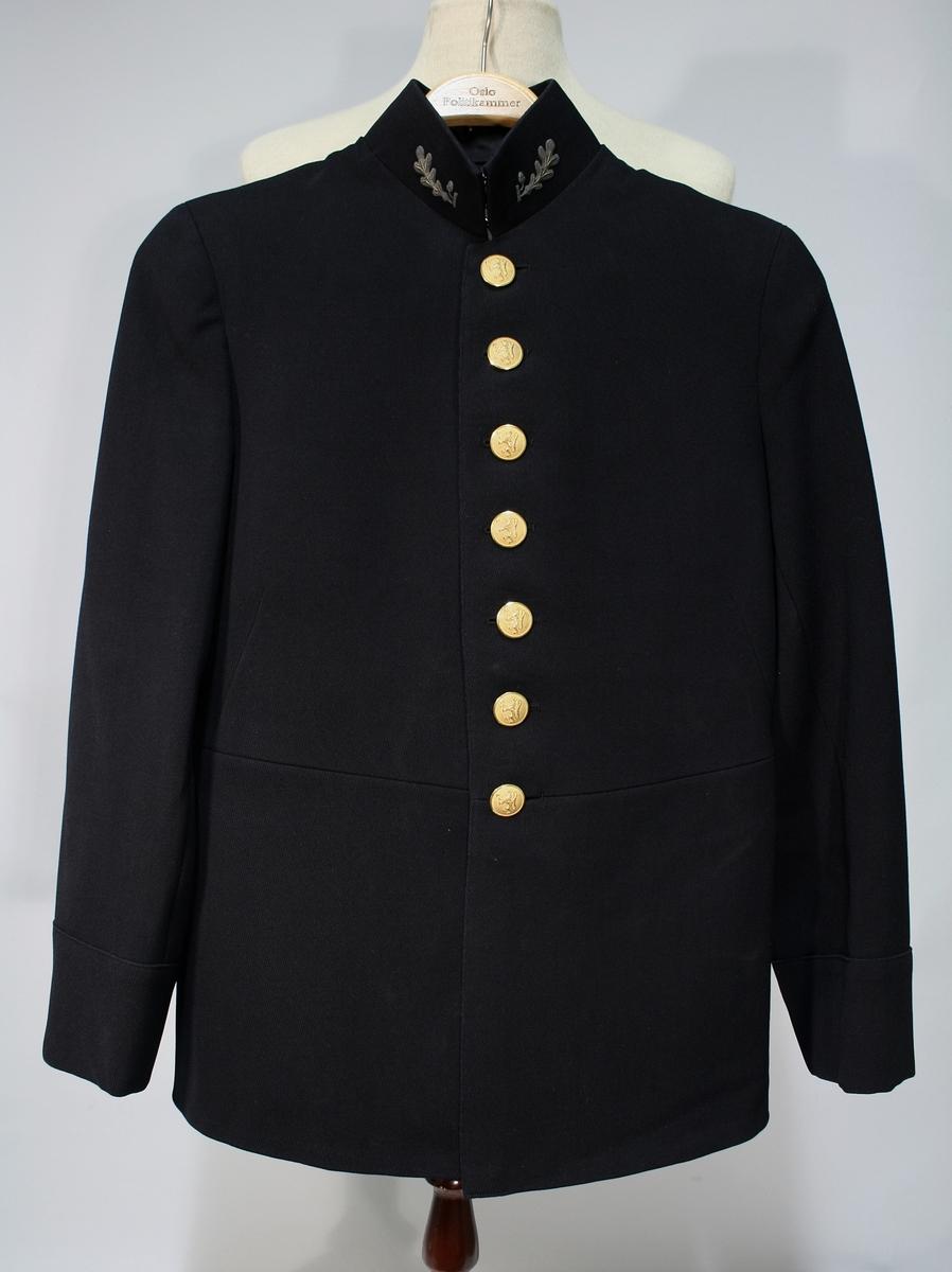 Mørkeblå uniformsjakke enkeltspent med syv riksløveknapper og oppstående stiv krage med broderte ekeløveblad. Ingen lommer. Bak en brett (splitt) med seks riksløveknapper. Tre riksløveknapper på ermene.