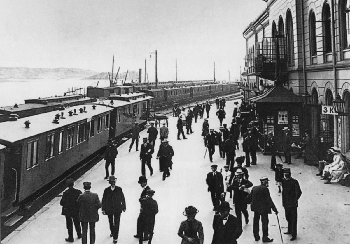Drammen jernbanestasjon med flere tog og mange reisende på plattformen.