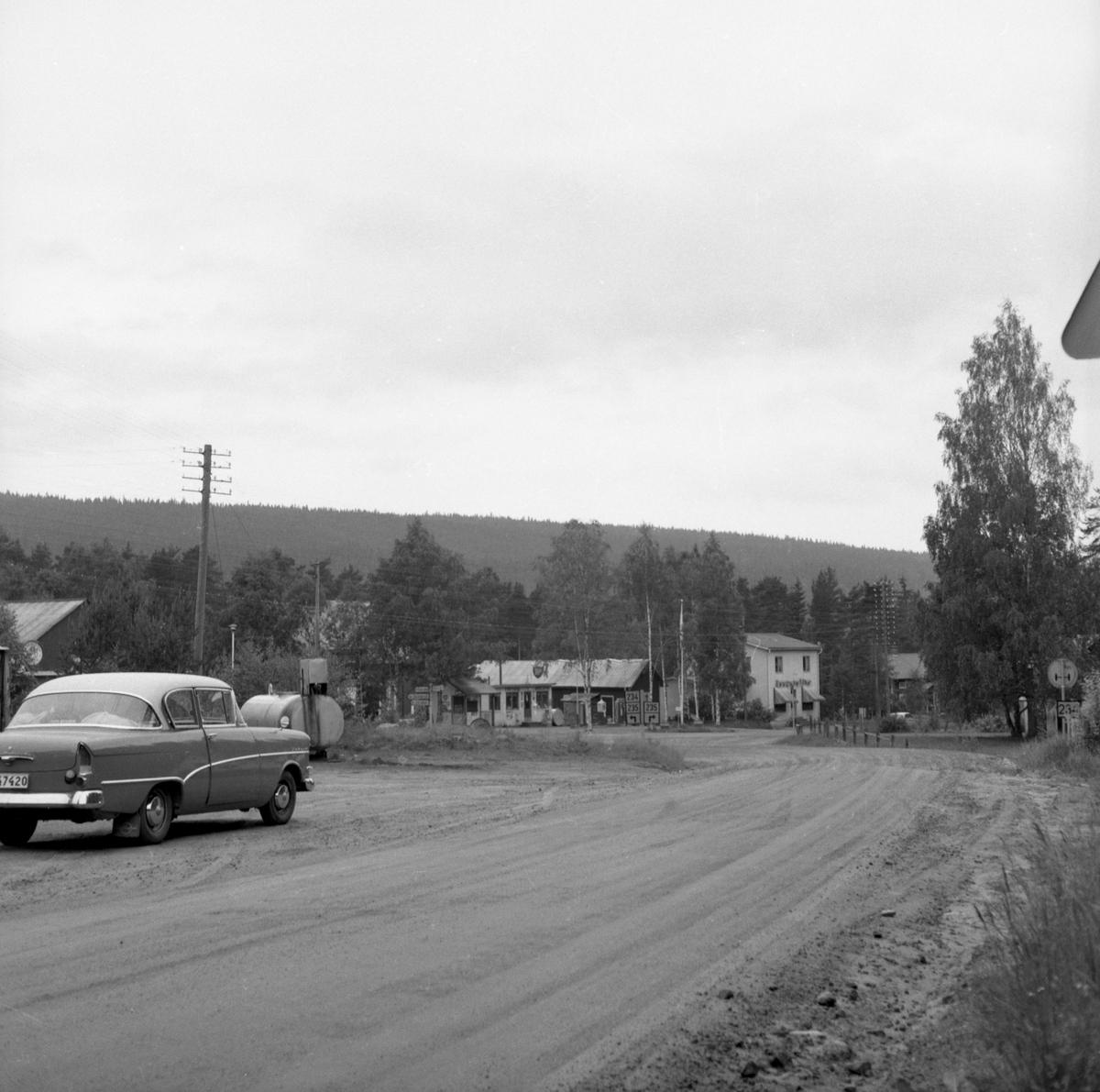 Bilden föreställer infarten till Värnäs från väg E45/E16. Rakt fram ser man BP-macken ägd av Olof Persson. Det stora vita huset inhyste Kooperativa Förbundets affär (Konsum), Koppra i folkmun. Förestods av Ragnhild Persson. Från slutet av 1950-talet: Värnäs, Stöllet.