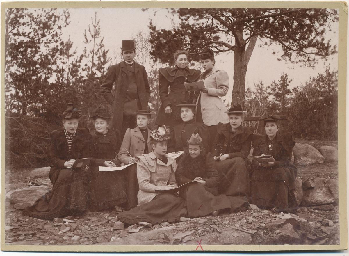 Otto Valstad sammen med mange kvinner med tegnesaker. Tilla Valstad sitter fremst til høyre.
