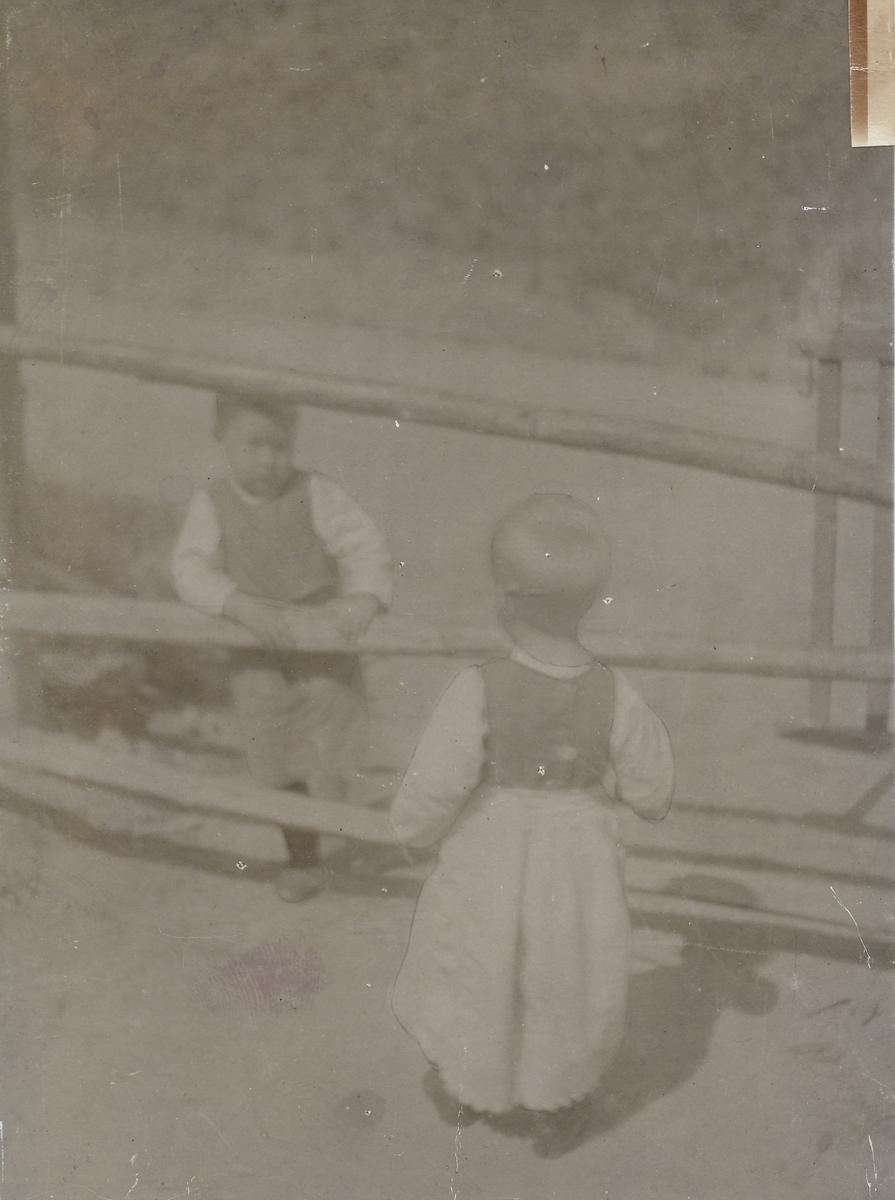 To små barn på hver sin side av et gjerde.